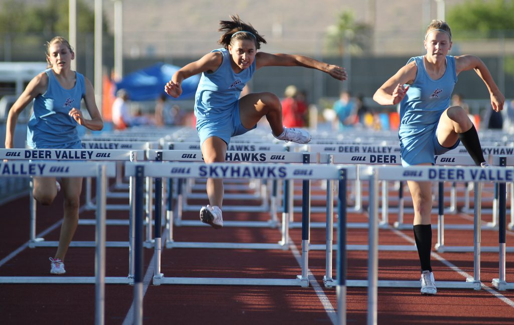Runners jumping over hurdles