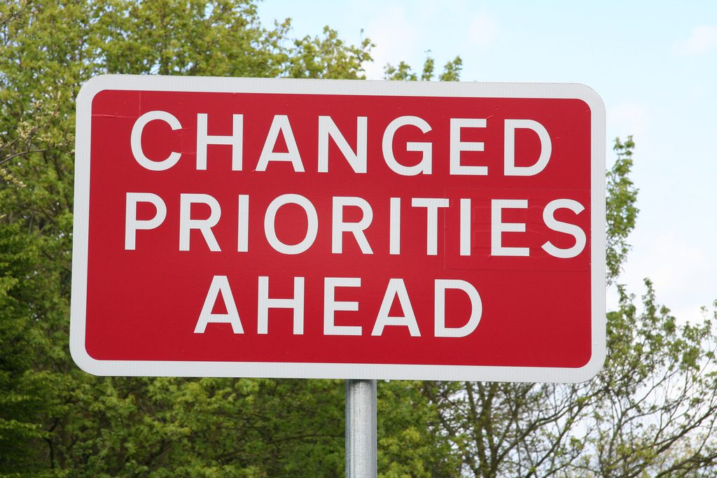 "Red sign that reads ""Changed Priorities Ahead"""