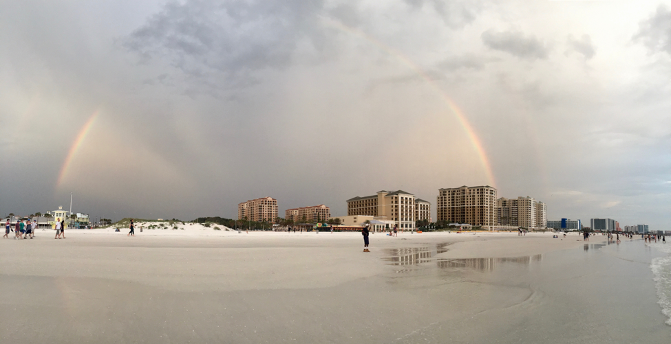 Rainbow over buildings and a beach
