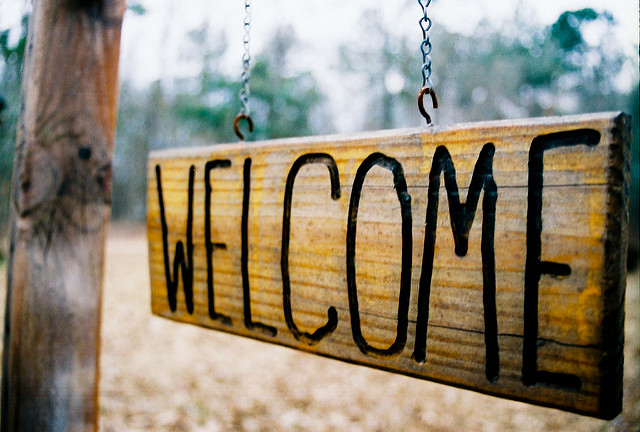 "Hanging wooden sign that reads ""Welcome"""
