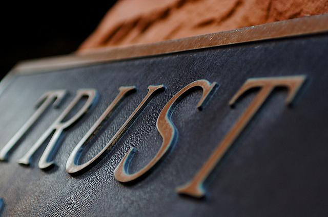 """Closeup of a metal plaque reading """"Trust"""""""