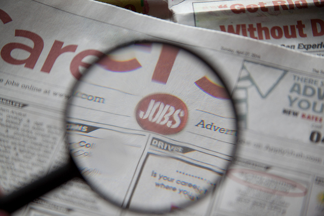 "Magnifying glass highlighting the word ""Jobs"" in a newspaper"